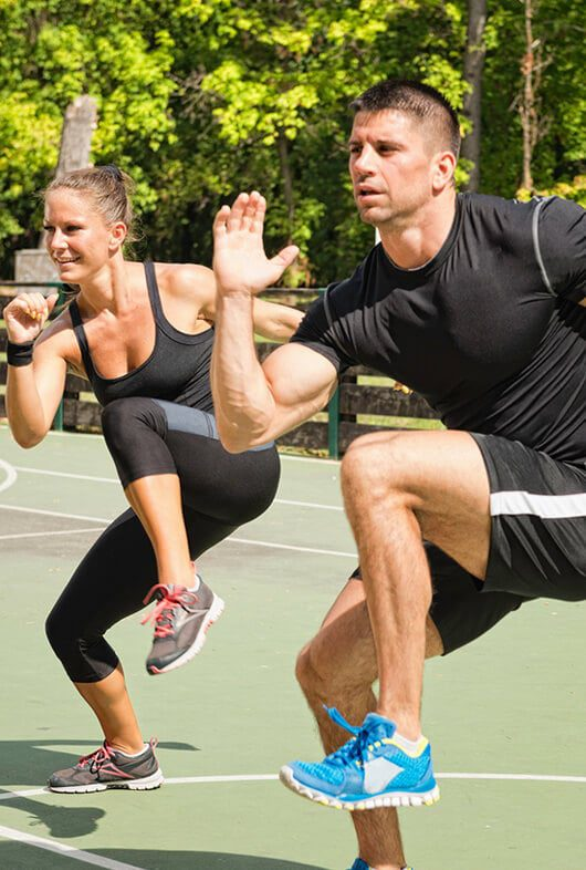 Couple performing knees to elbow in standing position