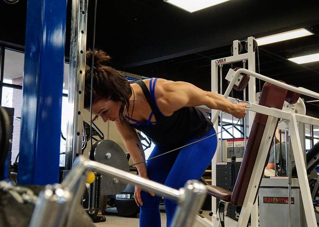 Lady doing cable tricep kickbacks