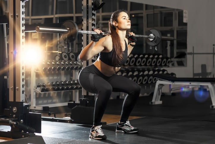 Girl with weights on Squat Rack