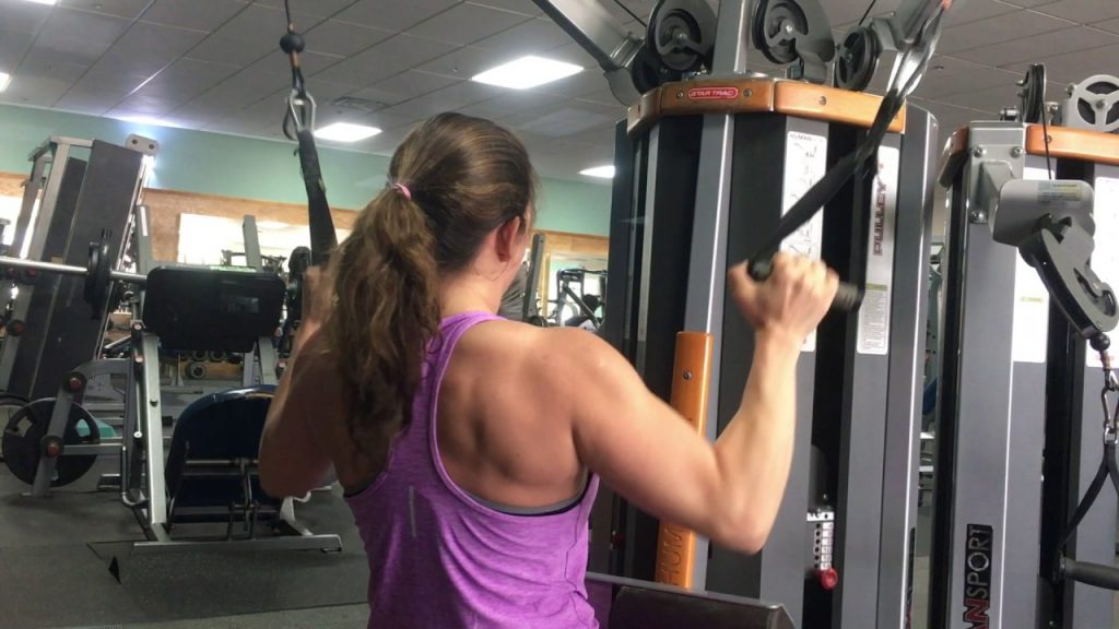 Lady using a dual cable lat pulldown machine